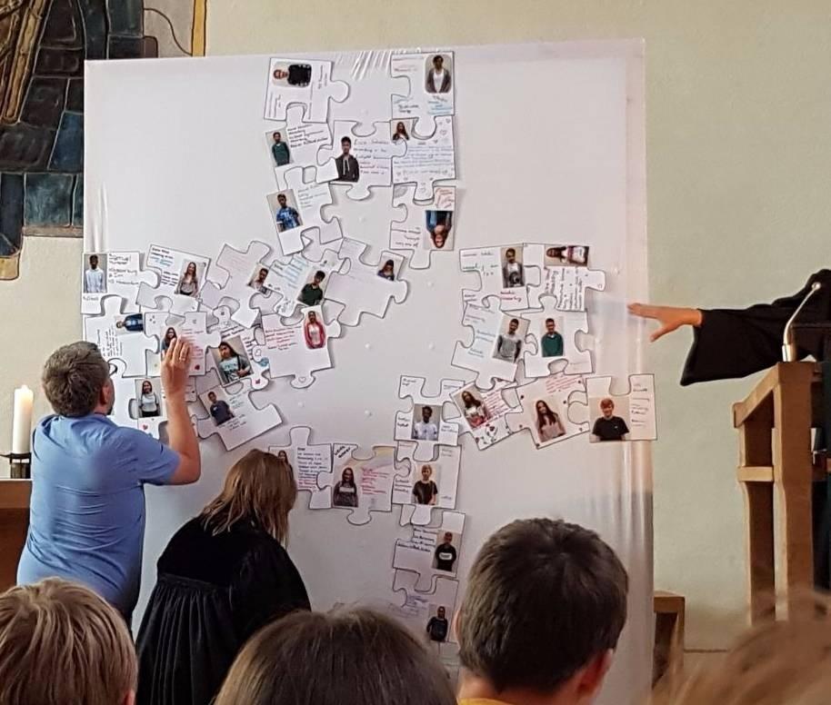 ein Kreuz entsteht aus Puzzle-Teilen